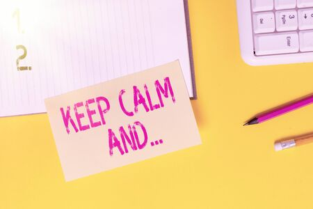 Text sign showing Keep Calm And. Business photo text motivational poster produced by British government Empty orange paper with copy space on the yellow table
