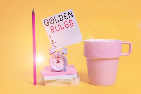 Word writing text Golden Rules. Business photo showcasing basic principle that should always follow to ensure success Alarm clock coffee cup note stacked notepads pencil colored background