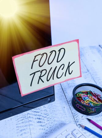 Writing note showing Food Truck. Business concept for a large vehicle with facilities for cooking and selling food Note paper taped to black computer screen near keyboard and stationary