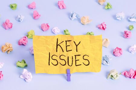 Handwriting text writing Key Issues. Conceptual photo vital or unsettled matter that showing are arguing about Colored crumpled papers empty reminder blue floor background clothespin