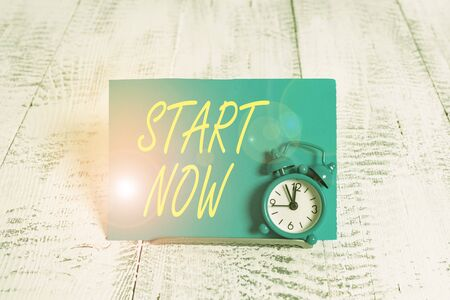 Handwriting text Start Now. Conceptual photo do not hesitate get working or doing stuff right away Mini blue alarm clock stand tilted above buffer wire in front of notepaper