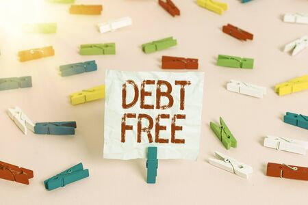 Writing note showing Debt Free. Business concept for does not owning any money to any individual or companies Colored clothespin papers empty reminder pink floor office pin