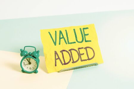 Handwriting text Value Added. Conceptual photo the extra value created over and above the original value Mini size alarm clock beside a Paper sheet placed tilted on pastel backdrop