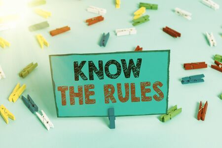 Writing note showing Know The Rules. Business concept for set explicit or regulation principles governing conduct Colored clothespin papers empty reminder blue floor officepin