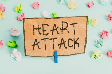 Handwriting text writing Heart Attack. Conceptual photo sudden occurrence of coronary thrombosis resulting in death Colored crumpled papers empty reminder blue floor background clothespin