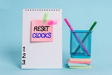 Text sign showing Reset Clocks. Business photo showcasing To revisit return to or recreate a time or era from the past Spiral notebook sticky note banners stacked pads pens holder pastel back