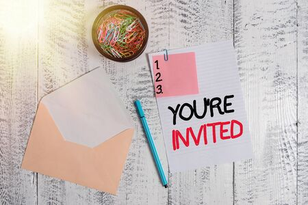 Word writing text You Re Invited. Business photo showcasing make a polite friendly request to someone go somewhere Envelope sheet paper sticky note ballpoint clips holder wooden background