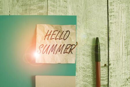 Text sign showing Hello Summer. Business photo showcasing season after spring and before autumn where the weather is hot Wrinkle paper and cardboard plus stationary placed above wooden background