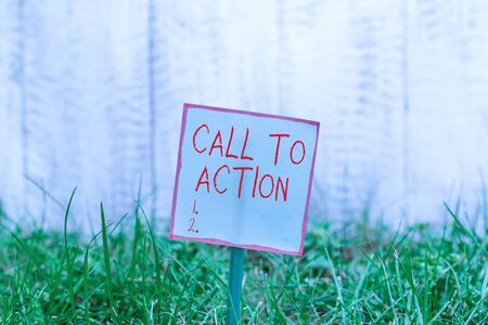 Word writing text Call To Action. Business photo showcasing exhortation do something in order achieve aim with problem Plain empty paper attached to a stick and placed in the green grassy land