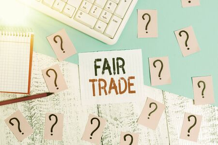 Word writing text Fair Trade. Business photo showcasing buying goods directly from producers in developing countries Writing tools, computer stuff and math book sheet on top of wooden table