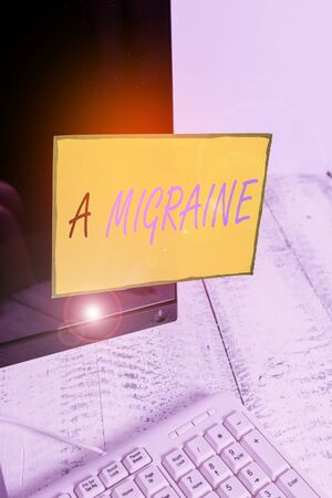 Writing note showing A Migraine. Business concept for recurrent throbbing headache that affects one side of the head Notation paper computer monitor screen near white keyboard