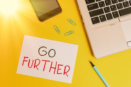 Writing note showing Go Further. Business concept for To make a bolder statement about something being discussed Trendy laptop smartphone marker paper sheet clips colored background Banque d'images