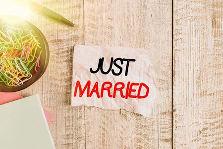 Text sign showing Just Married. Business photo text someone who has recently married or undergo matrimony Wrinkle paper and notebook plus stationary placed above wooden background