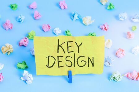 Handwriting text writing Key Design. Conceptual photo a necessary or very important realization of a concept or idea Colored crumpled papers empty reminder blue floor background clothespin
