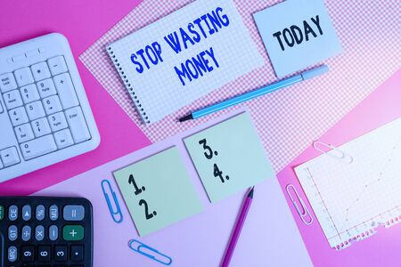 Word writing text Stop Wasting Money. Business photo showcasing advicing demonstrating or group to start saving and use it wisely Writing equipments and computer stuffs placed above colored plain table Archivio Fotografico