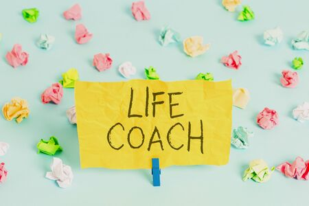 Handwriting text writing Life Coach. Conceptual photo someone who helps identify your goals and plan to achieve them Colored crumpled papers empty reminder blue floor background clothespin
