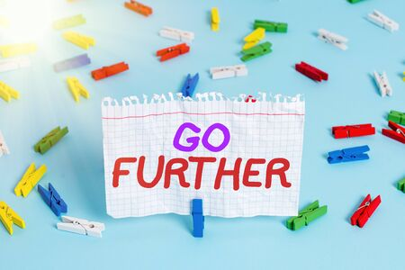 Conceptual hand writing showing Go Further. Concept meaning To make a bolder statement about something being discussed Colored clothespin paper empty reminder blue floor officepin Banque d'images