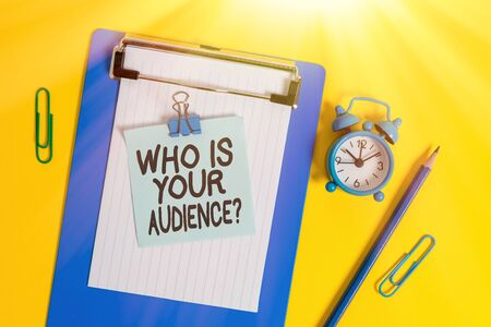 Conceptual hand writing showing Who Is Your Audience Question. Concept meaning who is watching or listening to it Clipboard sheet note pencil clips alarm clock colored background