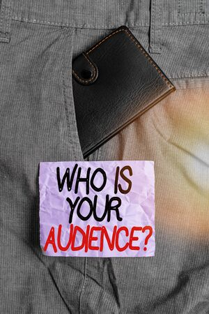 Conceptual hand writing showing Who Is Your Audience Question. Concept meaning who is watching or listening to it Small wallet inside trouser front pocket near notation paper 版權商用圖片
