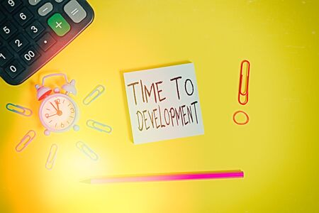 Word writing text Time To Development. Business photo showcasing a length of time during which a company grows or develop Alarm clock calculator clips rubber band pencil notepad colored background