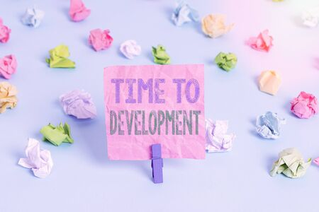 Conceptual hand writing showing Time To Development. Concept meaning a length of time during which a company grows or develop Colored crumpled papers empty reminder blue floor clothespin Stock Photo