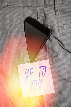Text sign showing Up To You. Business photo showcasing it is used to indicate a decision or choices of an individual Smartphone device inside formal work trousers front pocket near note paper Stock Photo