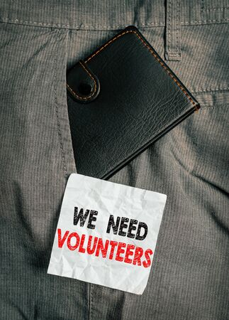 Word writing text We Need Volunteers. Business photo showcasing someone who does work without being paid for it Small little wallet inside man trousers front pocket near notation paper 版權商用圖片