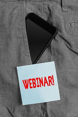 Conceptual hand writing showing Webinar. Concept meaning a seminar or other presentation that takes place on the Internet Smartphone device inside trousers front pocket note paper