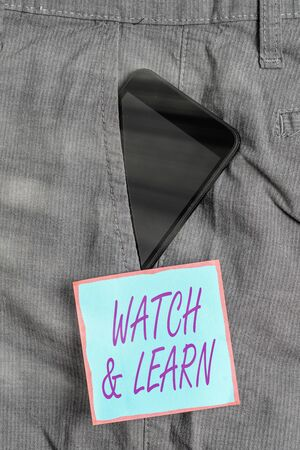 Word writing text Watch And Learn. Business photo showcasing demonstrating an action or ideas of how to do things Smartphone device inside formal work trousers front pocket near note paper