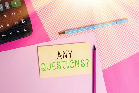 Writing note showing Any Questions Question. Business concept for you say write order to ask demonstrating about something writing equipments and plain note paper placed on the table