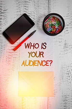 Writing note showing Who Is Your Audience Question. Business concept for who is watching or listening to it Smartphone paper sheet clips pen envelope wooden vintage background