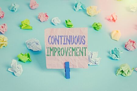 Conceptual hand writing showing Continuous Improvement. Concept meaning ongoing effort to improve products or processes Colored crumpled papers empty reminder blue floor clothespin