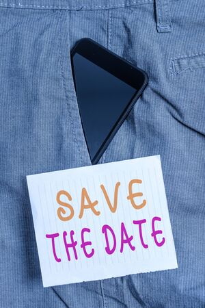 Writing note showing Save The Date. Business concept for Organizing events well make day special event organizers Smartphone device inside trousers front pocket note paper 版權商用圖片