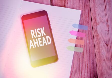 Writing note showing Risk Ahead. Business concept for A probability or threat of damage, injury, liability, loss Striped note book colored arrow banners smartphone wooden background 版權商用圖片