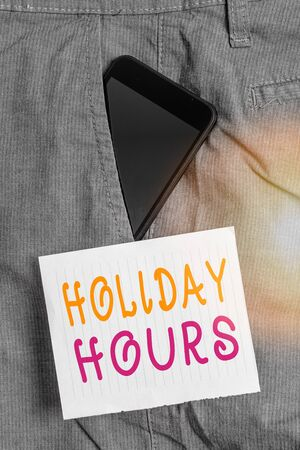Writing note showing Holiday Hours. Business concept for Overtime work on for employees under flexible work schedules Smartphone device inside trousers front pocket note paper