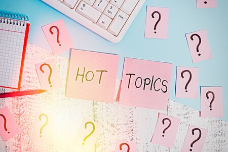 Text sign showing Hot Topics. Business photo showcasing subject that a lot of showing are arguing and discussing Writing tools, computer stuff and math book sheet on top of wooden table