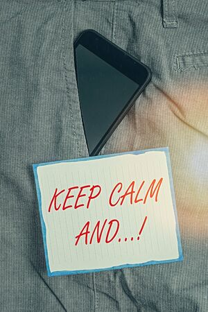 Conceptual hand writing showing Keep Calm And. Concept meaning motivational poster produced by British government Smartphone device inside trousers front pocket note paper 版權商用圖片