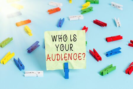 Writing note showing Who Is Your Audience Question. Business concept for who is watching or listening to it Colored clothespin papers empty reminder blue floor officepin