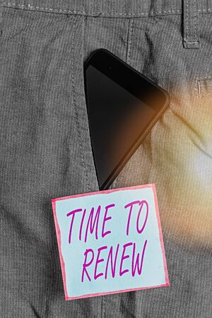 Word writing text Time To Renew. Business photo showcasing extending the period of time when something is valid Smartphone device inside formal work trousers front pocket near note paper