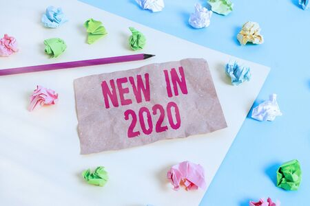 Text sign showing New In 2020. Business photo text what will be expecting or new creation for the year 2020 Colored crumpled papers empty reminder blue yellow background clothespin 版權商用圖片