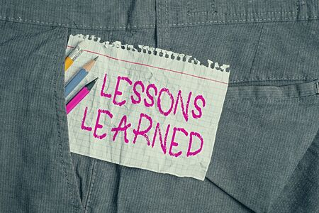Writing note showing Lessons Learned. Business concept for the knowledge or understanding gained by experience Writing equipment and white note paper inside pocket of trousers