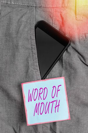 Word writing text Word Of Mouth. Business photo showcasing information that is transmitted without being written down Smartphone device inside formal work trousers front pocket near note paper 版權商用圖片