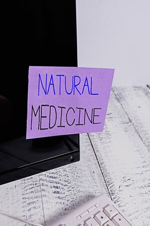 Text sign showing Natural Medicine. Business photo showcasing any of various systems of healing or treating disease Notation paper taped to black computer monitor screen near white keyboard