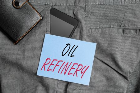 Writing note showing Oil Refinery. Business concept for industrial process of converting crude oil into petroleum Smartphone device inside trousers front pocket with wallet
