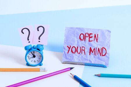 Text sign showing Open Your Mind. Business photo showcasing to be able to understand different ideas or ways of thinking Mini size alarm clock beside stationary placed tilted on pastel backdrop