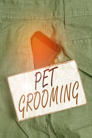 Text sign showing Pet Grooming. Business photo showcasing hygienic care and enhancing the appearance of the pets Smartphone device inside formal work trousers front pocket near note paper Imagens