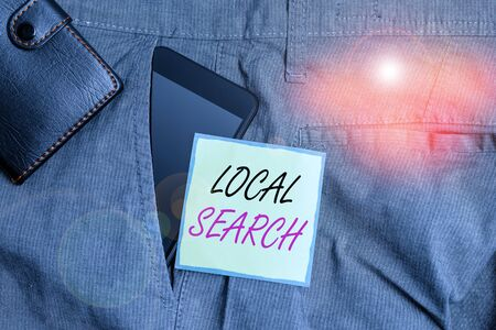 Text sign showing Local Search. Business photo text searches of a structured database of local business listings Smartphone device inside trousers front pocket with wallet and note paper