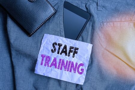 Word writing text Staff Training. Business photo showcasing learn specific knowledge improve performance in current roles Smartphone device inside trousers front pocket with wallet and note paper 版權商用圖片