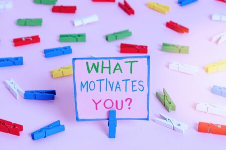Word writing text What Motivates Youquestion. Business photo showcasing know reasons why you want to wake up each morning Colored clothespin papers empty reminder pink floor background office pin