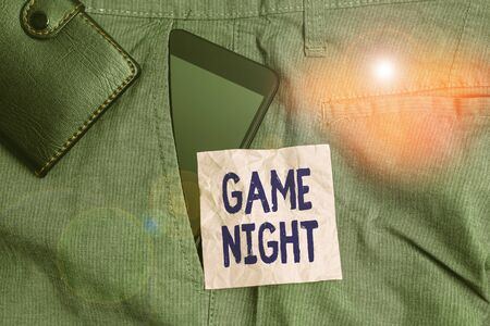 Text sign showing Game Night. Business photo showcasing usually its called on adult play dates like poker with friends Smartphone device inside trousers front pocket with wallet and note paper 版權商用圖片